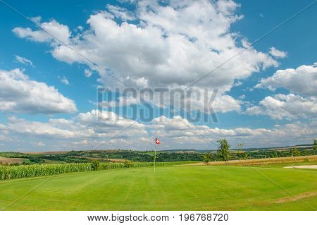 Golf course landscape. Golf field with green grass red flag and cloudy blue sky
