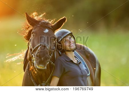 Young woman rider with her horse enjoying good mood in evening sunset light. Outdoor lifestyle photography