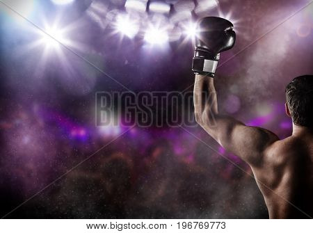 Close-up of man boxer with raised hand in victory gesture. Concept of hard sport, glory and success. Free space for text. High resolution image