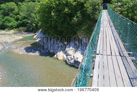View of walking suspension bridge and mountain river of left