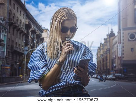 Teenage girl in a striped stylish shirt and jeans smoking electronic cigar