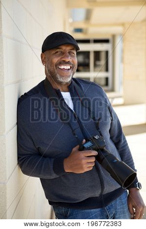 Mature African American Man Smiling Holding A Camera