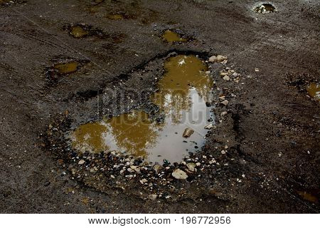 Photo of a large road pit on asphalt pavement