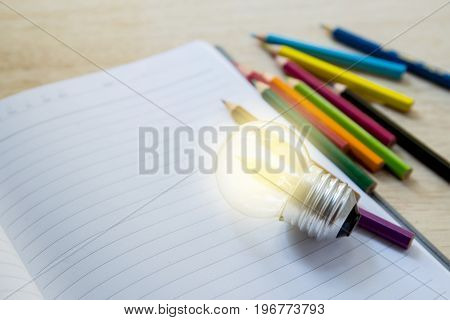 Pencil color crayon on notebook with light bulb