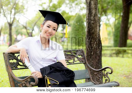 Joyful Student Celebrating His Graduation Seated On A Bench In A Park And Holding Certificate, Educa