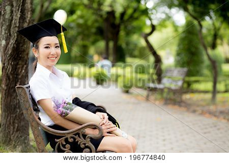 Joyful Student Celebrating His Graduation Seated On A Bench In A Park And Holding Flower With Congra