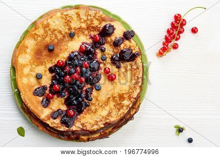 Thin pancakes with summer berries on white wooden table. Top view