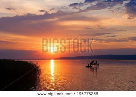 Sunset over Lake Balaton with anglers' silhouettes in Hungary