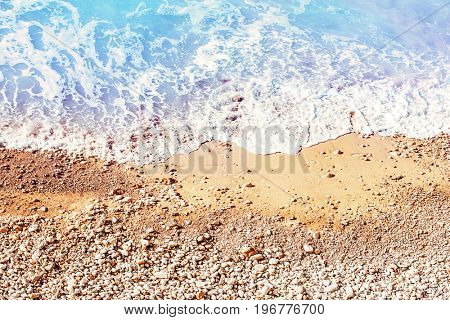 Beautiful coastline, sandy beach with pebbles washed by the sea shore waters, tropical resort background, summer vacation concept