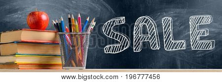 Back to School sale. Accessories, books and fresh apple against chalkboard
