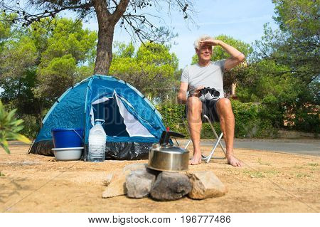 Man camping alone with blue dome tent and spyglass for adventure