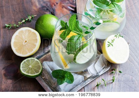 Refreshing cold iced mint drink with lemons and lime summer drink with ice selective focus toned image