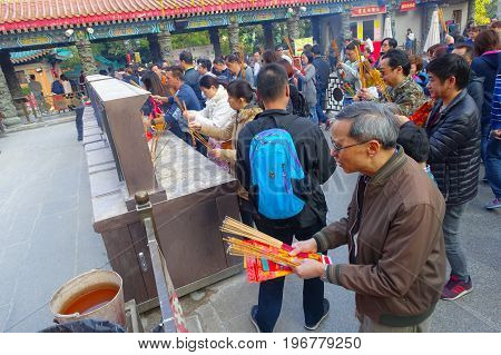 HONG KONG, CHINA - JANUARY 22, 2017: Crowd of people holding a their hands an incense sticks in a sunny day, inside of Wong Tai Sin Buddhist Temple to pray, in Hong Kong, China.