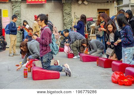 HONG KONG, CHINA - JANUARY 22, 2017: Unidentified people praying over their knees in a red soft pad inside of Wong Tai Sin Buddhist Temple to pray, in Hong Kong, China.