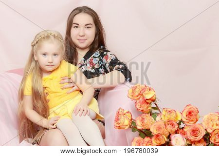 Sisters grow old and younger hugs on the couch.Near a bouquet of tea roses.