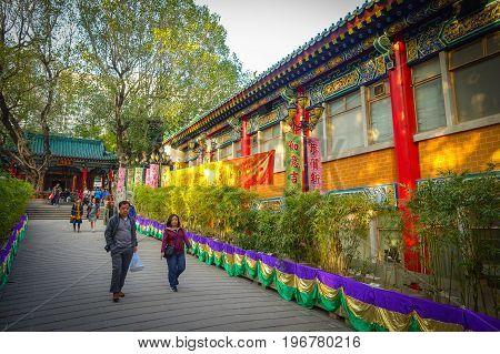 HONG KONG, CHINA - JANUARY 22, 2017: Unidentified people walking through the enter of Wong Tai Sin Buddhist Temple to pray, in Hong Kong, China.