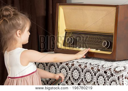 Curious little girl looking at a vintage radio . She is trying to push on the keys.