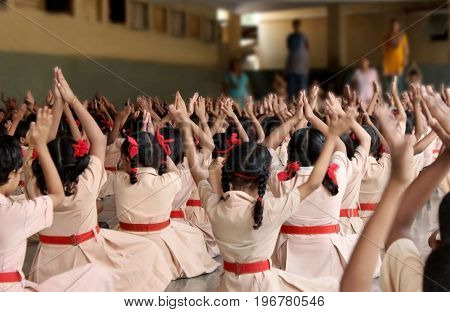 School children doing yoga with the teachers