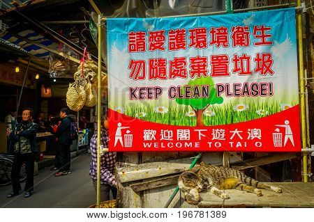 HONG KONG, CHINA - JANUARY 26, 2017: Informative sign in english and chinesse in a market in fishermen town in lantau, with a cat resting in front, in Hong Kong, China.