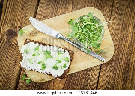 Slice Of Bread With Fresh Cutted Cress And Cream Cheese On An Old Wooden Table