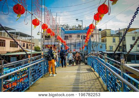 HONG KONG, CHINA - JANUARY 26, 2017: Unidentified people taking selfies over a bridge in a fishermen town in lantau, Hong Kong, China.