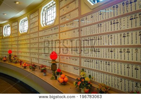 HONG KONG, CHINA - JANUARY 26, 2017: Inside of a building in Tian Tin monastery, with some pictures and names in the wall, with plastic flowers and fruits as oblation in Lantau Island, Hong Kong.