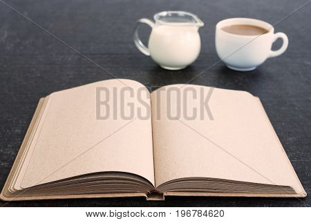 Time for coffee and diary. An old diary with empty pages with a cup of coffee and a jar of milk on a shabby black background. Soft focus, focus on a diary.