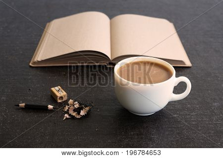 Time for coffee and diary. A cup of coffee, a just sharpened little pencil and an open diary with empty pages on a shabby black background. Soft focus on a cup.