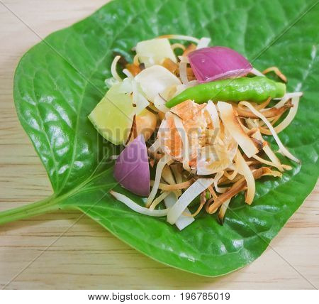 Thai Traditional Snack and Dessert Close Up Dish of Miang Kum or Sweet and Spicy Betel Leaf Wrap Filled with Coconut Peanuts Dried Shrimp Chiles and Lime.
