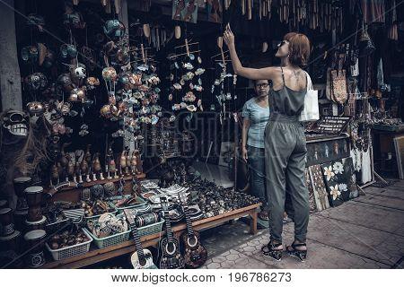 BALI, INDONESIA -JANUARY 1, 2017: Young woman on the souvenir street of Ubud, Bali