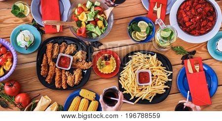 Top view group of people having dinner together while sitting at wooden table