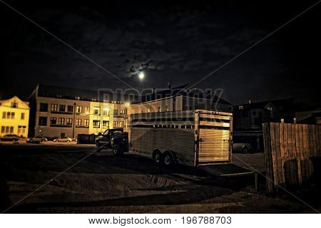A truck with a horse trailer in a city parking lot at night right next to a dark alley with a fence. Night sky with dramatic clouds and the moon.