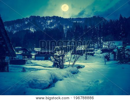 Snow covered the ground in winter season. Silhouette of town with night sky clouds and bright full moon serenity nature background. High contrast. The moon taken with my own camera.