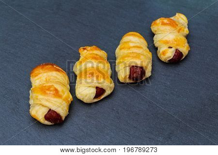 Home made pigs in a blanket. Sausages rolled in croissant dough baked cooling on metal rack.