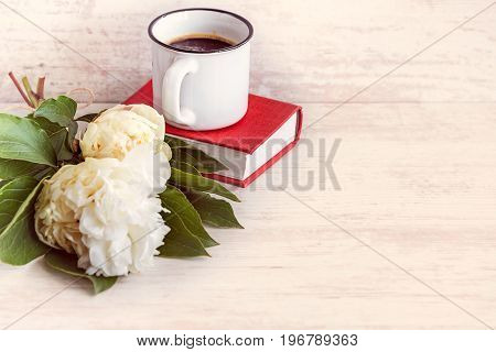 A cup of coffee white peonies and a red book over a white wooden background.