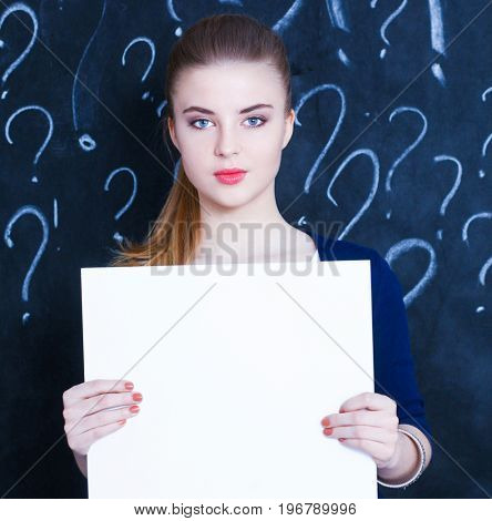 Young girl with question mark with blank on a gray background