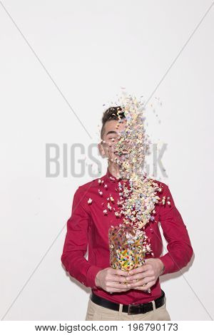 One Teenager Male, White Background, Studio Portrait, Red Shirt, Pants, Throwing Confetti, Smiling,