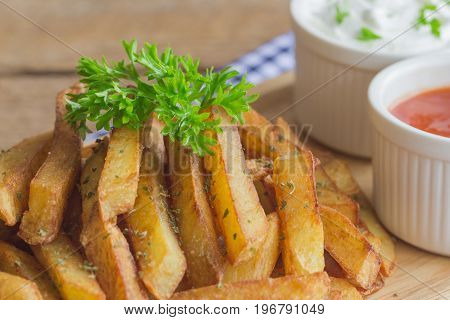 Homemade french fries serve with ketchup and sour cream or mayonnaise. Golden brown crispy french fries sprinkle with salt and oregano on wood plate for snack or appetizer. French fries on wood table. Close up concept on french fries.