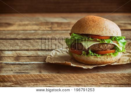 Homemade hamburger on brown paper. Delicious sandwich hamburger with meat or pork ham cheese and fresh vegetable. Hamburger or sandwich is the popular fast food for brunch or lunch. Sandwich in burger style on wood table with copy space.