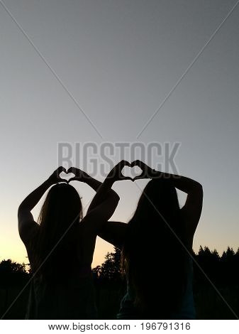 Best friends with interlocking arms and hands making hearts at dusk.