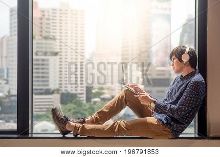 Young asian man relaxing enjoy watching movie from his laptop computer with headphones on glass window. Urban lifestyle in living space.