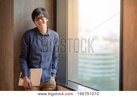 Young Asian man dressed in casual style holding laptop computer. high school or university college student educational concept