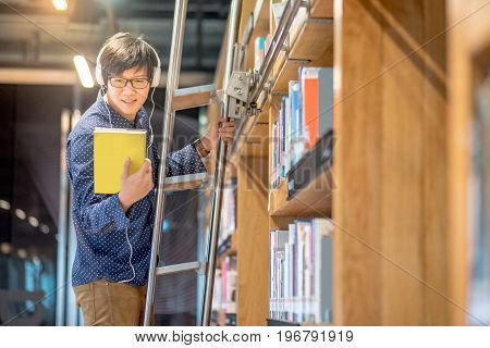 Young Asian man choosing book in bookshelf using ladder in library male student dressed in casual style. high school or university college educational concepts
