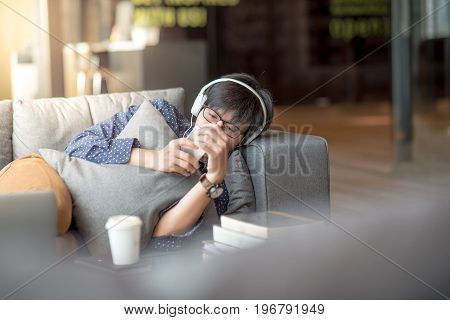 Young Asian man using smartphone taking a break relaxing on sofa during study in library high school or university college student educational concept