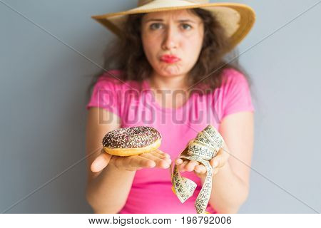 Confused young woman holding a donut and a measuring tape. The concept of healthy eating.Diet.