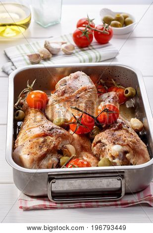Roasted turkey drumstick with cherry tomatoes green olives and garlic. Grilled turkey legs in cooking pan on white table.