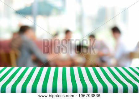 Table top covered with stripped tablecloth on blurred background of people in cafe - can be used for montage and display foods or products