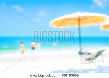 Blurred blue sea and white sand beach with parasol beach chair and some people - holiday and vacation background concept