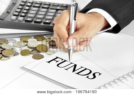 Hand with pen pointing to FUNDS word on the paper - financial and investment concept
