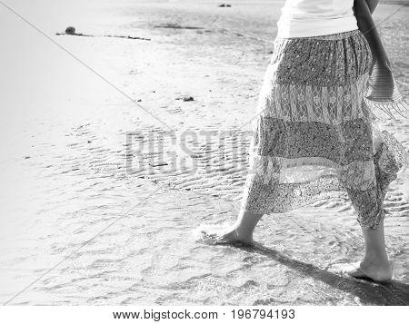 Beach travel - Black and white woman walking on sand beach. Closeup detail of female feet .Step up concept.